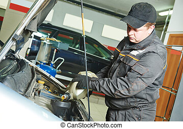 car mechanic pouring oil into motor engine