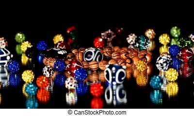 Different colorful beads on black background, rotation - A...