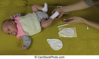 newborn footprint make - Happy mother create newborn baby...