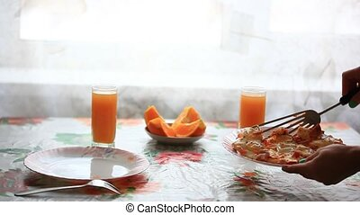 waitress lays eggs in a plate on the table. Breakfast with juice and oranges