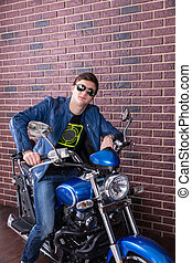 Cool dude sitting on his motorbike in trendy modern...