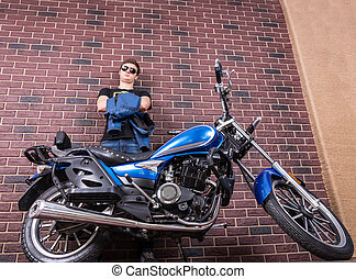 Man with Motorcycle Leaning Against Brick Wall - Low Angle...