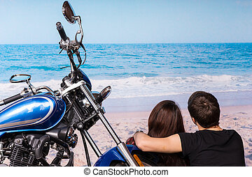Romantic couple at the beach with their motorbike sitting...