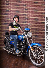 Portrait of Young Man on Motorcycle by Brick Wall - Full...