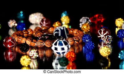 Different colorful beads on black background, cam moves to...
