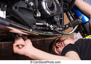 Young man doing maintenance on his motorbike