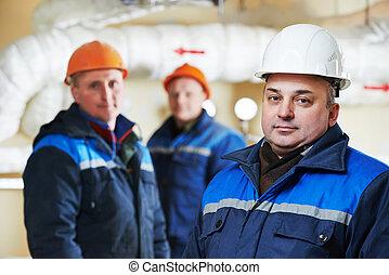heating engineer repairmans in boiler room - three repairman...
