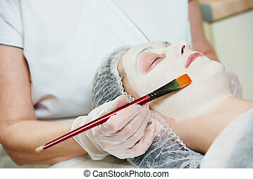 Spa cosmetologist applying facial mask - beautician worker...