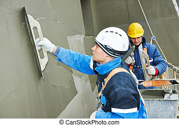 workers at plastering facade work - builders at facade...