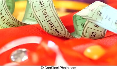 Measuring tape isolated on yellow and red clothes, close up...