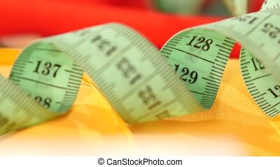 Measuring tape isolated on yellow cloth, close up -...