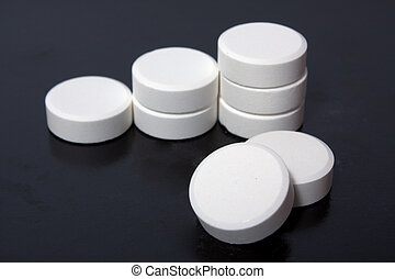 white tablets - heap of white tablets on black background