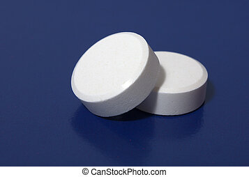 white tablets - heap of white tablets on dark blue...