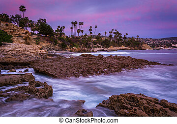 Rocks and waves in the Pacific Ocean at twilight, at...