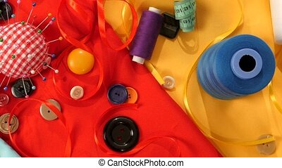 Colorful thread, buttons, pincushion, measuring tape on...