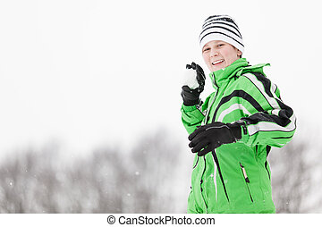 Playful young boy taking aim with a snowball smiling happily...
