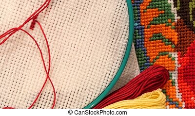 Hoop with thread and bright embroidery, flosses, close up -...