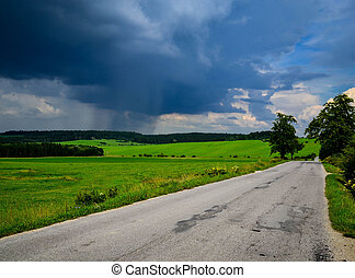 In the distance it rains - landscape with road and in the...