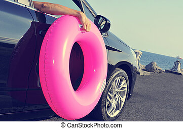 man holding a swim ring outside of the window of a car -...
