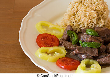 meat with brown rice and garnish on white plate