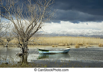 Calm Before the Storm - Fishermans boat in a pondlake...