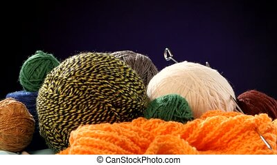 Different yarn balls with spokes on orange scarf, black background, rotation, cam moves to the left