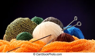 Varicolored yarn balls with spokes on orange scarf, black background, rotation, cam moves to the left