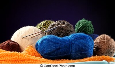 Colorful yarn balls with spokes on orange scarf, black background