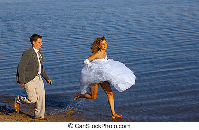 Running bride and fiance - Bride and fiance running near the...