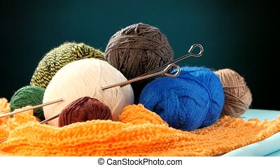 Varicolored yarn balls with spokes on orange scarf, brown background, rotation, cam moves to the right