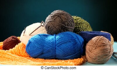 Varicolored yarn balls with spokes on orange scarf, blue background, rotation, cam moves to the left