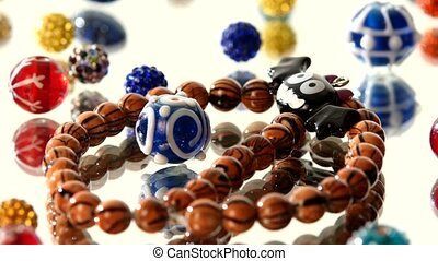 Colorful beads on white background, cam moves to the left,...
