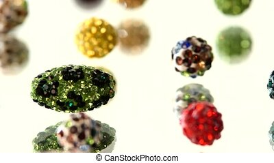 Varicolored, shiny beads on white background, cam moves to the left, rotation, close up