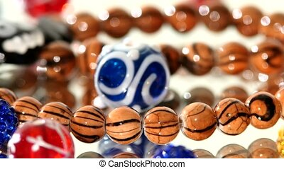 Motley, different colorful beads on white background, cam...