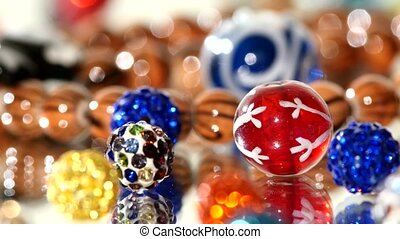 Different colors of beads on white background, rotation,...