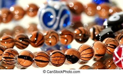 Multi colored beads on white background, rotation, close up...