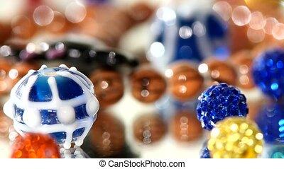 Shiny, beautiful beads on white background, rotation, close up