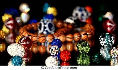 Lot of varicolored beads on black background, rotation, reflection