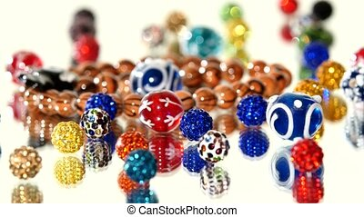 Lot of varicolored beads on white background, rotation, reflection