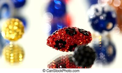 Red, blue, yellow and other color beads on white background, rotation, close up