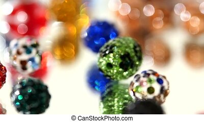 Lot of varicolored beads on white background, rotation, close up