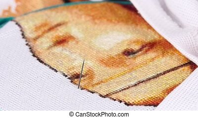 Woman sitting and making embroidery, close up, slow motion -...