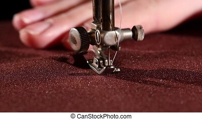 Old sewing machine on vinous cloth with woman`s hand, close...