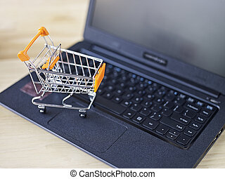 online shopping - toy shopping cart on top of laptop...