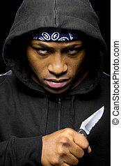 Criminal With a Knife - thug wearing a hoodie and holding a...