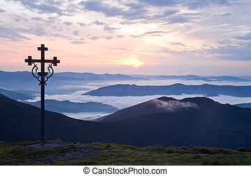 Summer sunrise mountain view with christianity cross