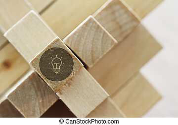 illuminated light bulb on a wooden block puzzle as...