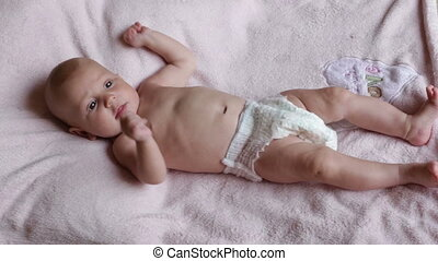 small baby girl lies on pink blanket waving little hands and...