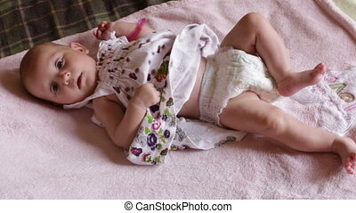 small baby girl in pretty dress lies on blanket