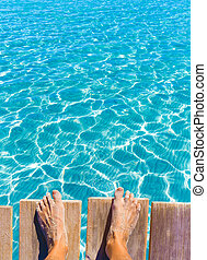 sandy feet on the pier tropical turquoise sea